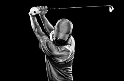 A b&w image of a golfer at the top of his swing.