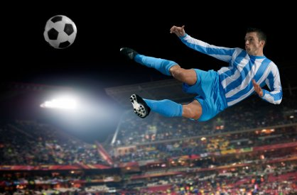 Soccer player kicking the ball, in mid air.